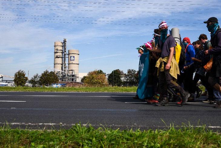 Marche activistes usine au loin